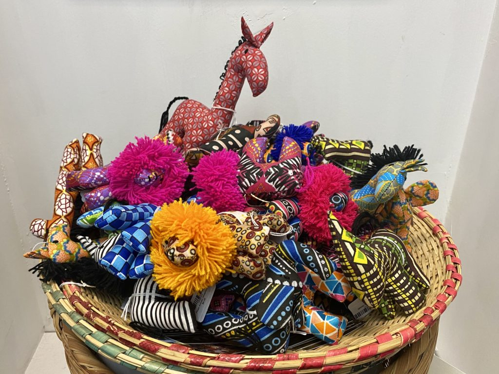 A basket full of petite, handmade stuffed animals, including lions, rhinoceros, zebras and giraffes, made from brightly colored fabric and yarn.